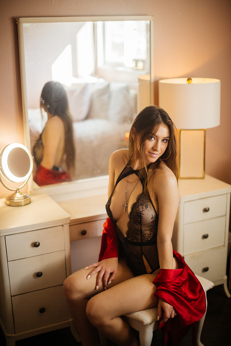 A beautiful young dirty blonde haired woman poses for a Thornton home boudoir studio photography session wearing black lingerie and a red robe sitting at a white vanity near Denver, Colorado
