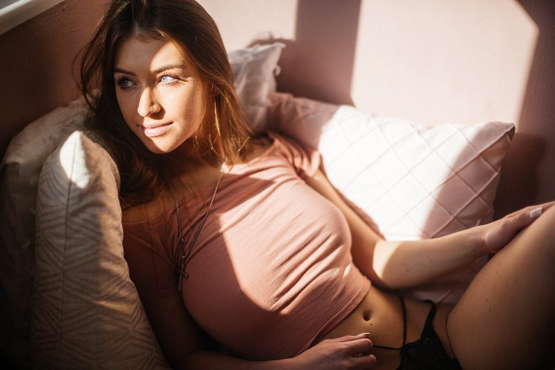 A beautiful young dirty blonde haired woman poses for a Thornton home boudoir studio photography session wearing a pink shirt with black underwear on a pink bed next to a window near Denver, Colorado