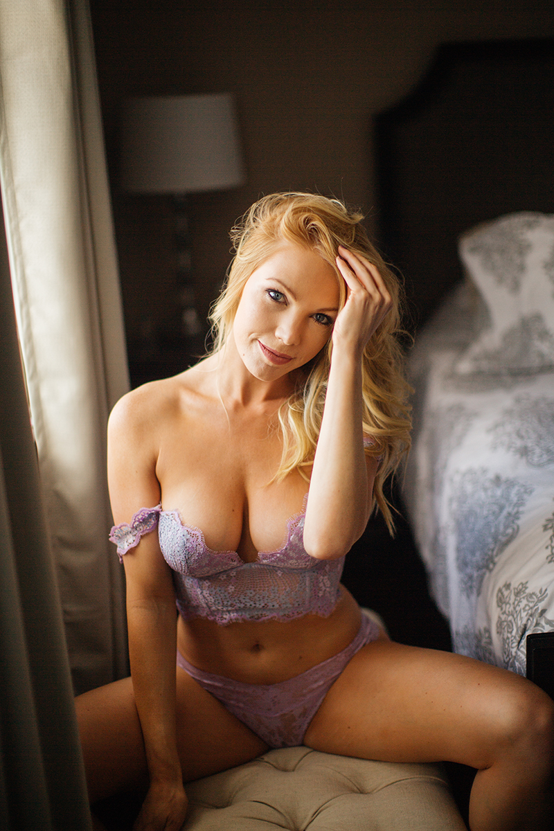 A beautiful young blonde female promo model poses for a Broomfield home boudoir photography session on a bench in her room near her bed in front of a window wearing a lavender bra and underwear set near Denver, Colorado