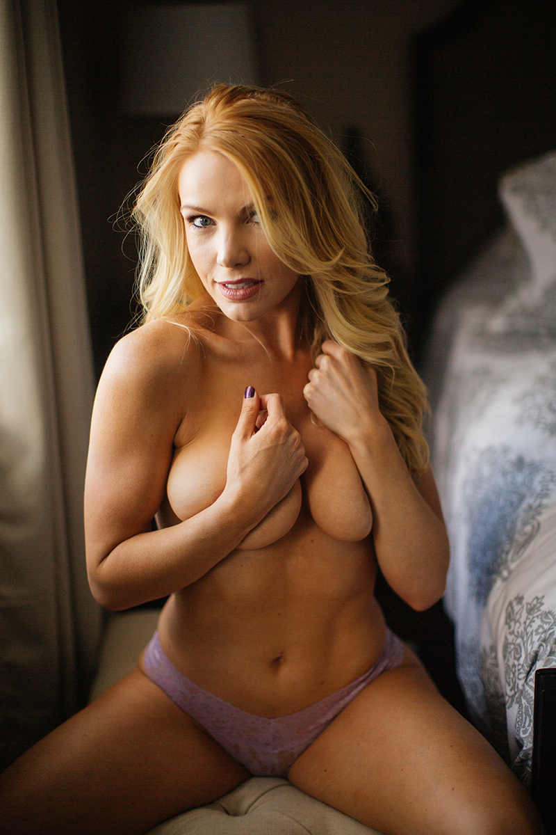 A beautiful young blonde female promo model poses topless for a Broomfield home boudoir photography session on a bench in her room near her bed in front of a window wearing lavender underwear near Denver, Colorado