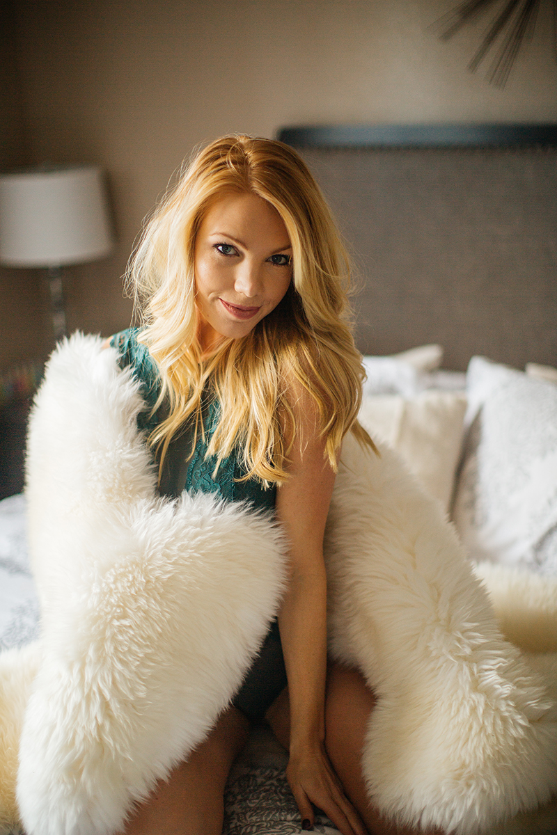 A beautiful young blonde female promo model poses for a Broomfield home boudoir photography session on her bed wrapped up in a fur rug in her room wearing green lingerie near Denver, Colorado