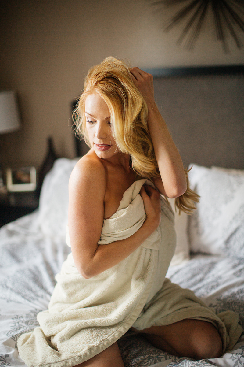 A beautiful young blonde female promo model poses topless for a Broomfield home boudoir photography session on her bed wrapped up in a fur rug in her room wearing green lingerie near Denver, Colorado