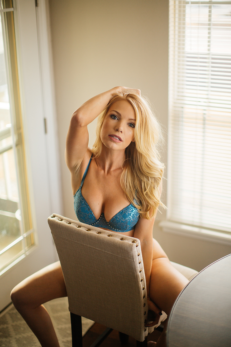A beautiful young blonde female promo model poses for a Broomfield home boudoir photography session at her dining room table sitting on a stool wearing a teal bra and underwear set near Denver, Colorado