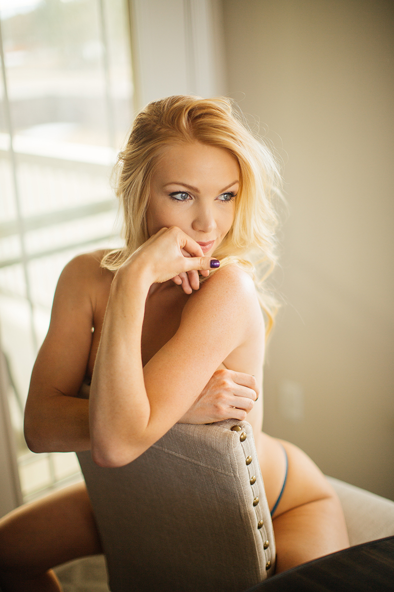 A beautiful young blonde female promo model poses topless for a Broomfield home boudoir photography session at her dining room table sitting on a stool wearing teal underwear near Denver, Colorado