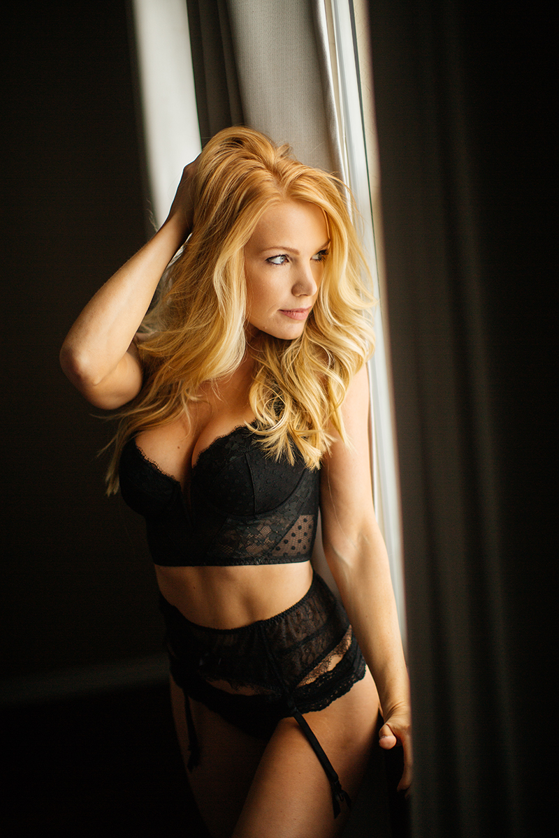 A beautiful young blonde female promo model poses for a Broomfield home boudoir photography session in her room in front of a window wearing a black lingerie set with a garter near Denver, Colorado