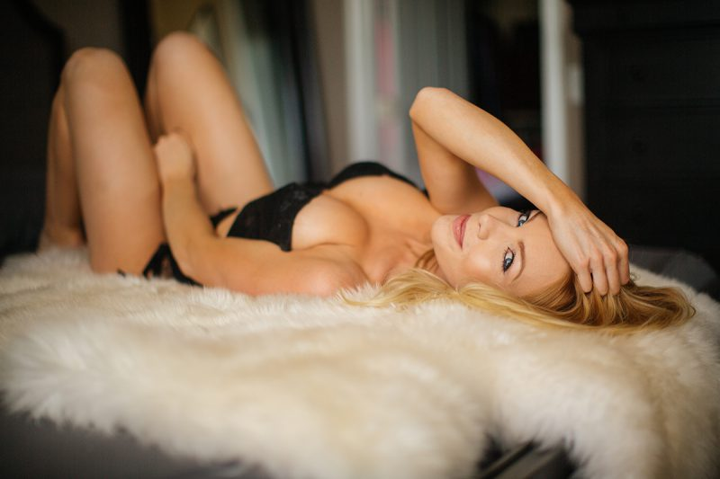 A beautiful young blonde female promo model poses for a Broomfield home boudoir photography session in her room on a fur rug on her bed wearing a black lingerie set with a garter near Denver, Colorado