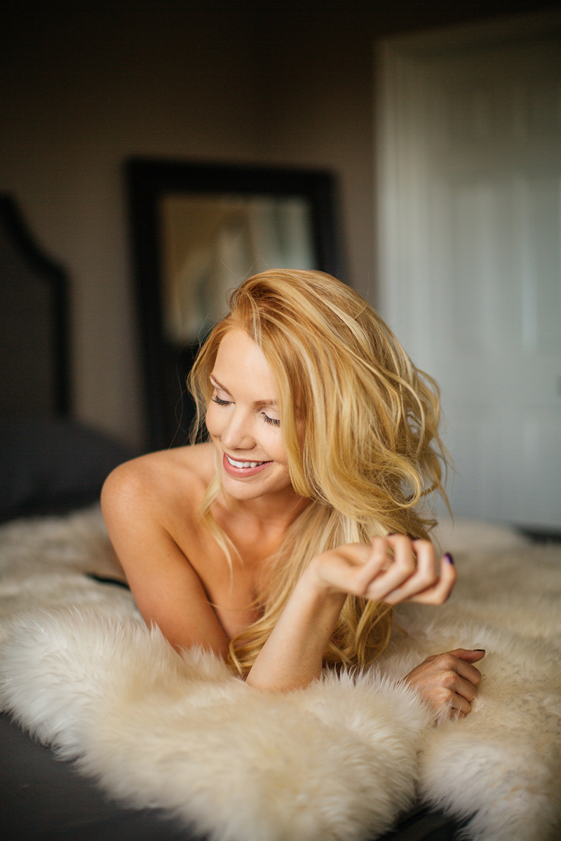 A beautiful young blonde female promo model poses topless for a Broomfield home boudoir photography session in her room on a fur rug on her bed wearing a black lingerie set with a garter near Denver, Colorado