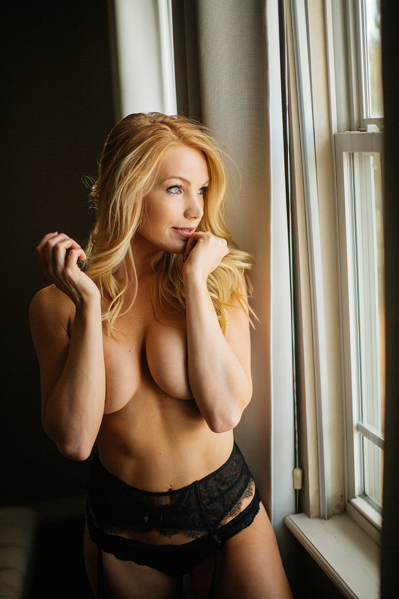 A beautiful young blonde female promo model poses topless for a Broomfield home boudoir photography session in her room in front of a window wearing a black lingerie set with a garter near Denver, Colorado