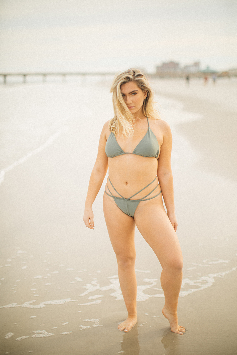 A beautiful young blonde woman poses for a Jacksonville Beach Pier boudoir photography session wearing a green bikini standing in the ocean in Florida
