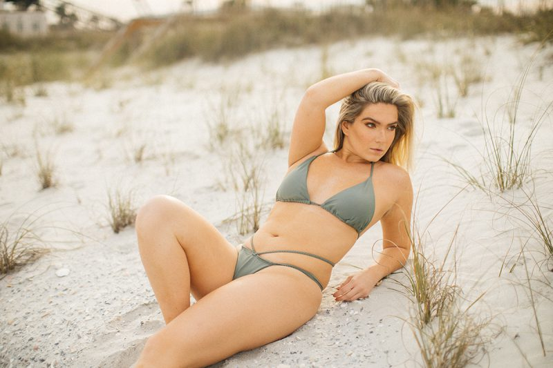 A beautiful young blonde woman poses for a Jacksonville Beach Pier boudoir photography session wearing a green bikini laying in the sand in Florida