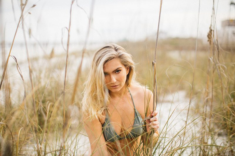 A beautiful young blonde woman poses for a Jacksonville Beach Pier boudoir photography session wearing a green bikini peeking through bushes in the sand in Florida