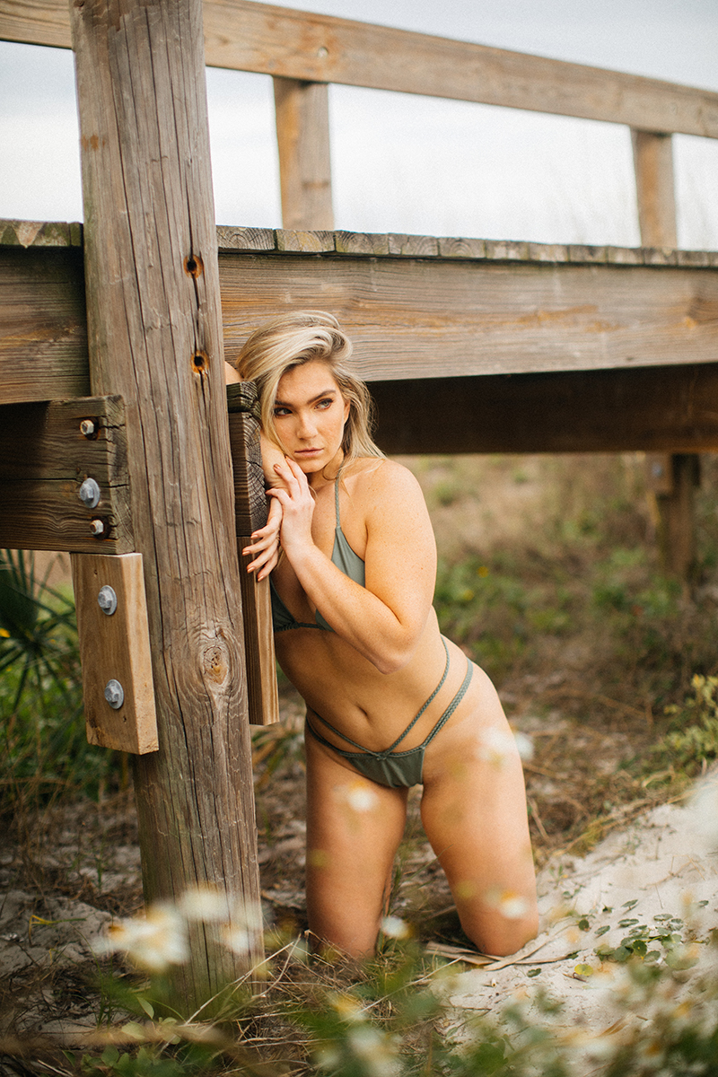 A beautiful young blonde woman poses for a Jacksonville Beach Pier boudoir photography session wearing a green bikini leaning against a wood bridge over sand in Florida