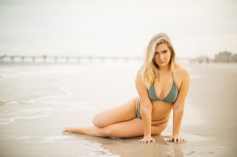 A beautiful young blonde woman poses for a Jacksonville Beach Pier boudoir photography session wearing a green bikini laying in the sand as the waves crash in on her in Florida