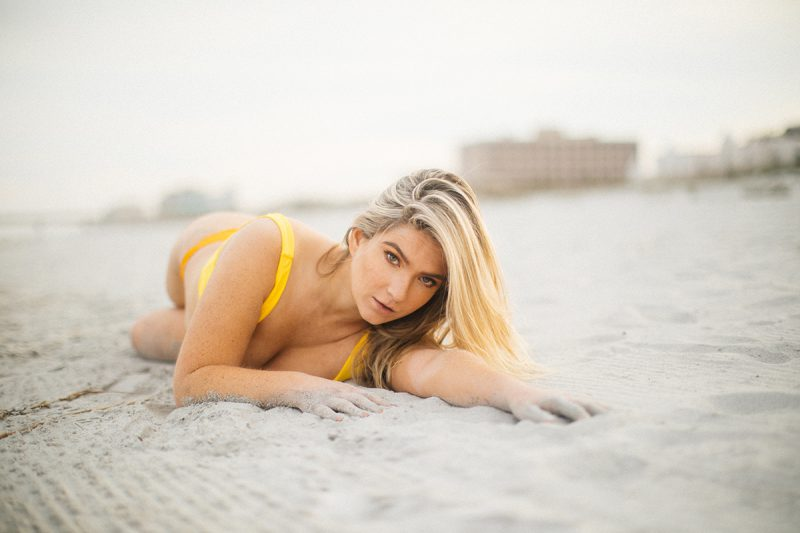 A beautiful young blonde woman poses for a Jacksonville Beach Pier boudoir photography session wearing a yellow bikini laying on the sand as the waves crash in on her in Florida