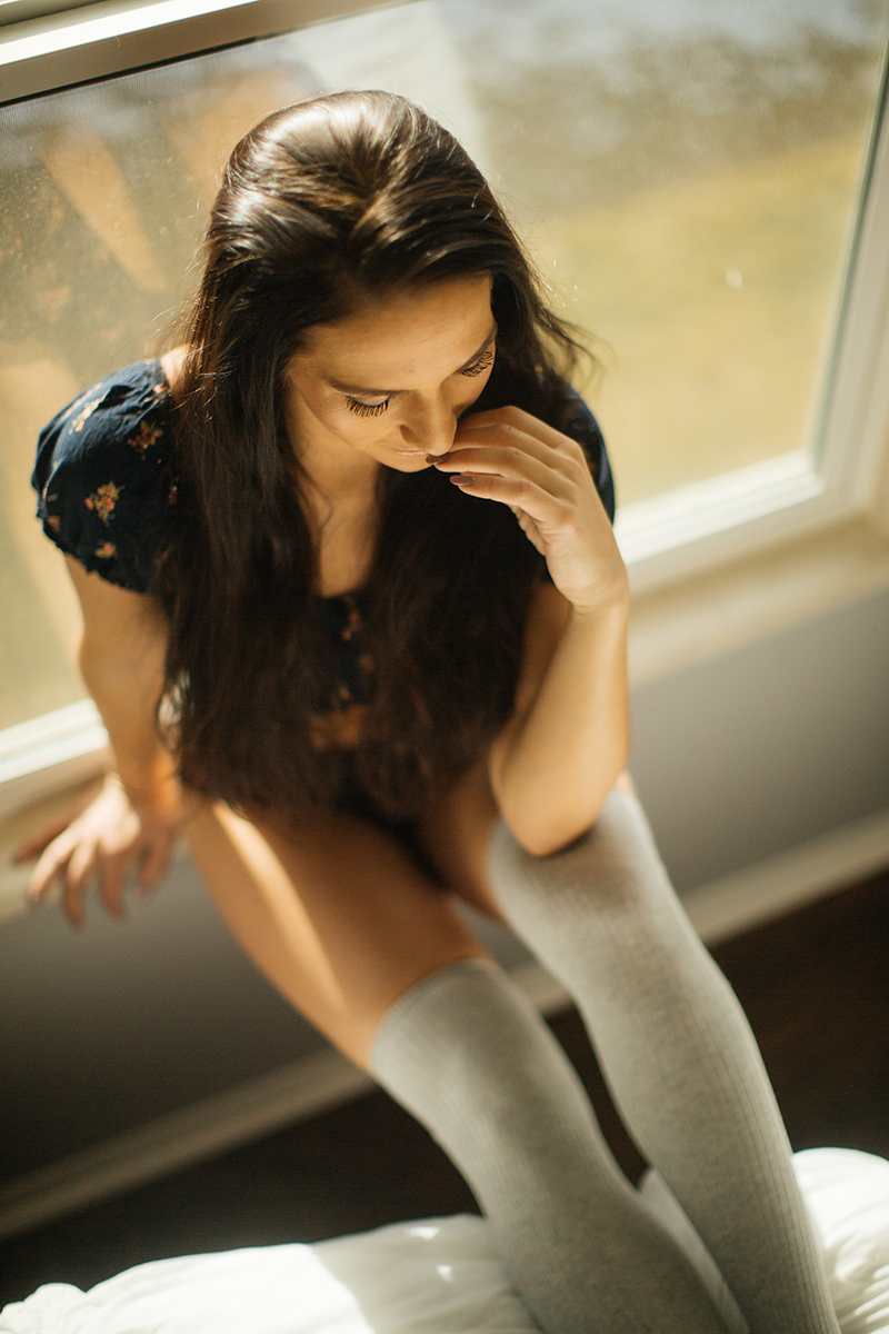 A beautiful young brunette poses for a Denver home studio boudoir photography wearing a blue floral crop top, black underwear and tan knee high socks sitting next to a window in Thornton, Colorado