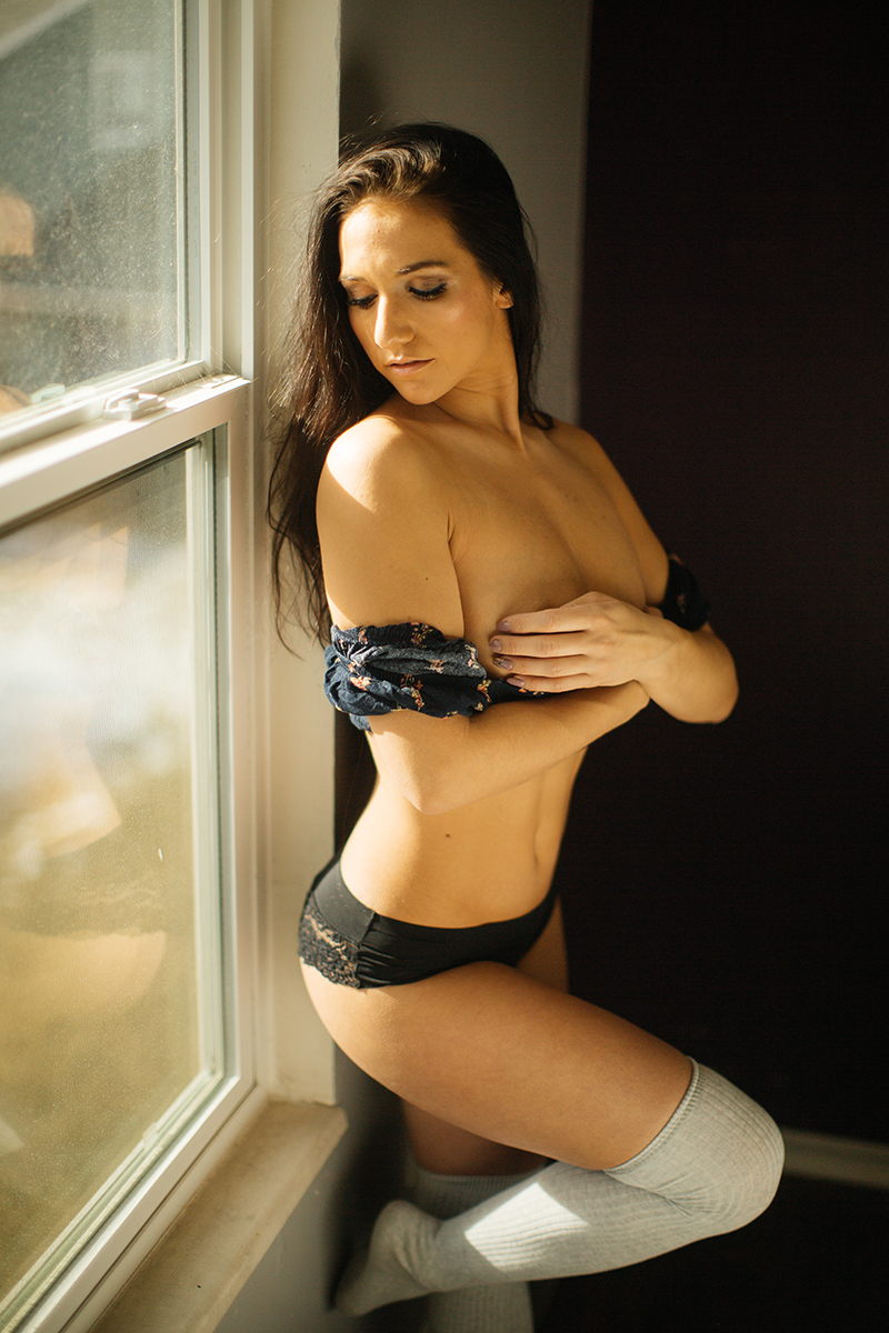 A beautiful young brunette poses topless for a Denver home studio boudoir photography wearing a blue floral crop top, black underwear and tan knee high socks standing next to a window in Thornton, Colorado