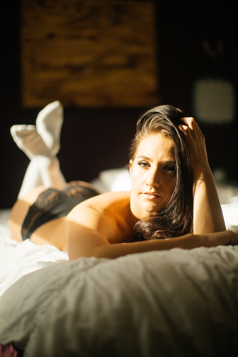 A beautiful young brunette poses topless for a Denver home studio boudoir photography wearing black underwear and tan knee high socks laying on a bed next to a window in Thornton, Colorado