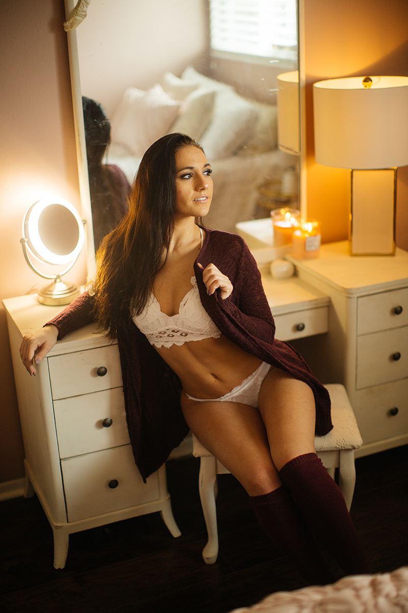 A beautiful young brunette poses for a Denver home studio boudoir photography wearing a white bra and underwear set with a red sweater and red knee high socks sitting at a white vanity in Thornton, Colorado