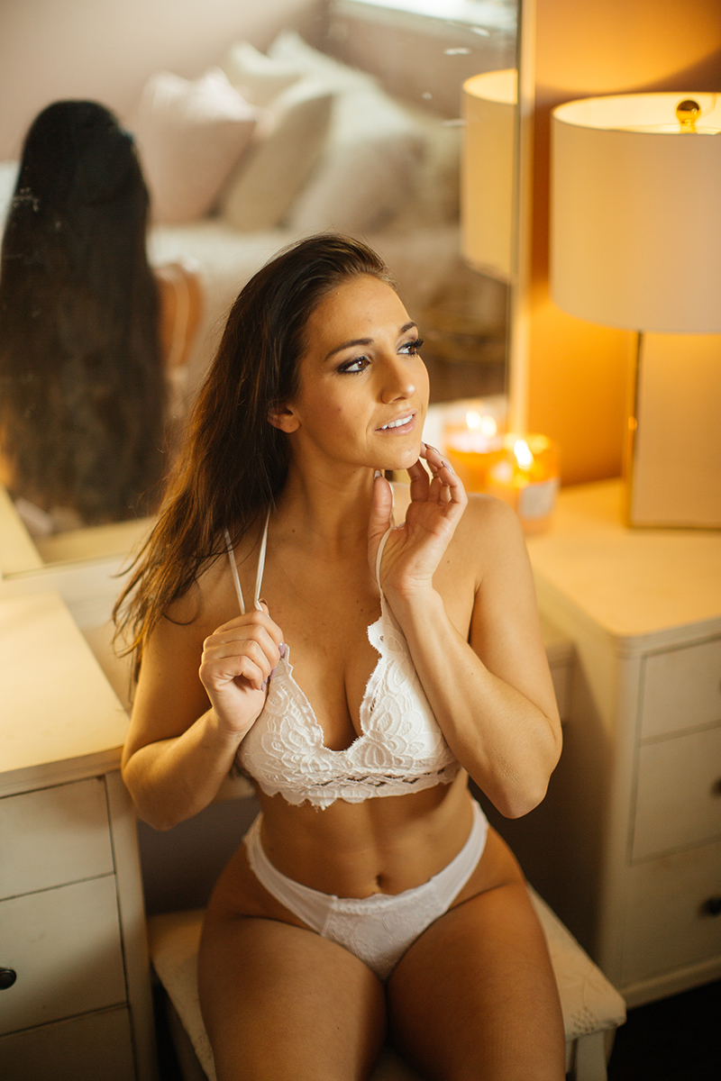 A beautiful young brunette poses for a Denver home studio boudoir photography wearing a white bra and underwear set with red knee high socks sitting at a white vanity in Thornton, Colorado