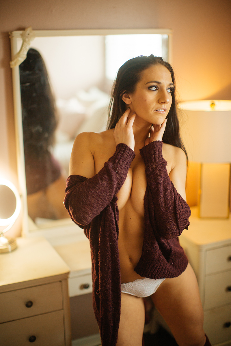 A beautiful young brunette poses topless for a Denver home studio boudoir photography wearing white underwear, a red sweater and red knee high socks standing in front of a white vanity in Thornton, Colorado
