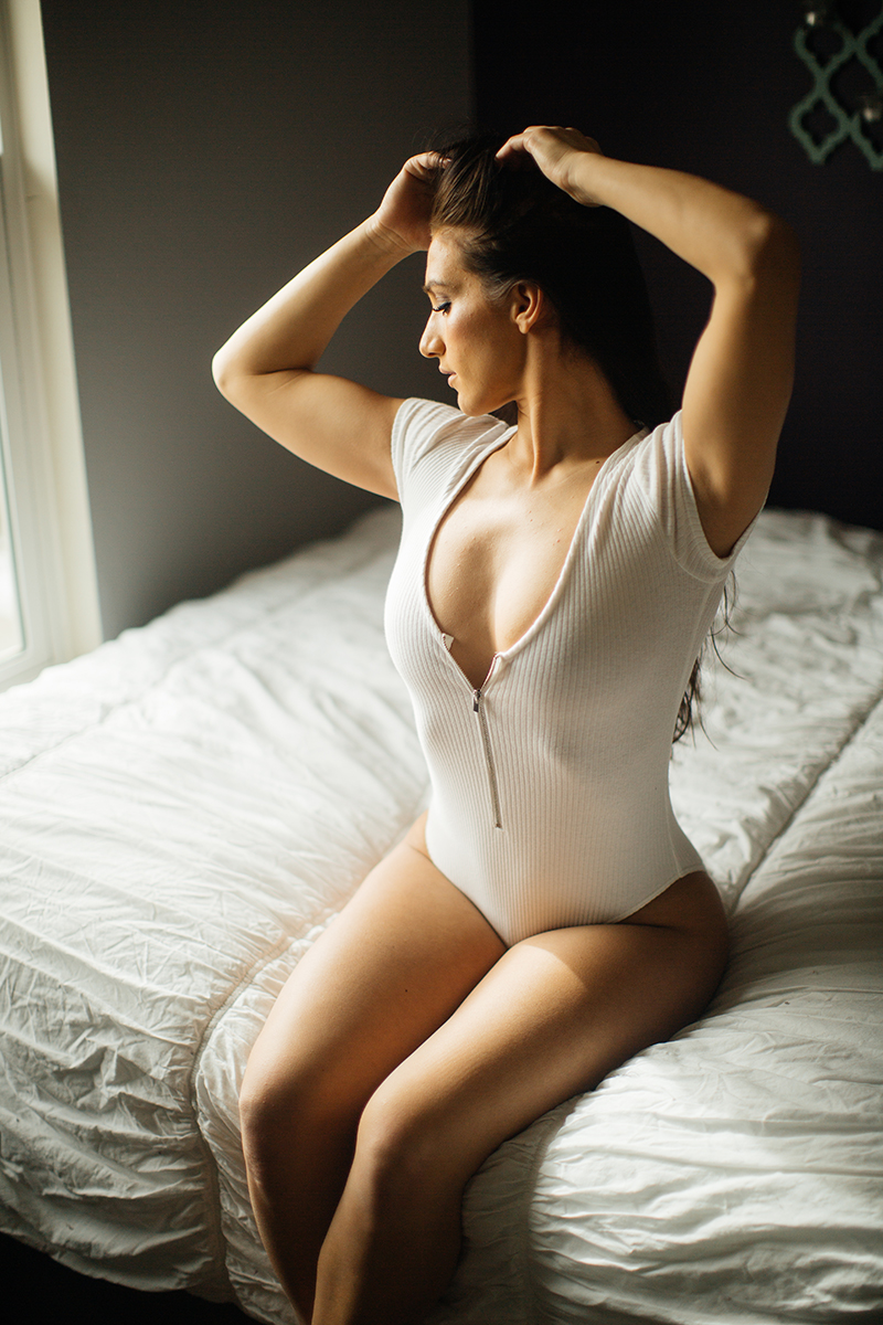A beautiful young brunette poses for a Denver home studio boudoir photography wearing a white body suit in sitting on a white bed in Thornton, Colorado