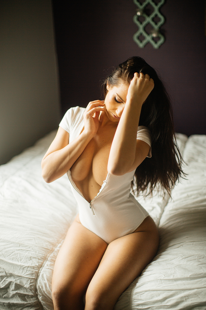A beautiful young brunette poses topless for a Denver home studio boudoir photography wearing a white body suit in sitting on a white bed in Thornton, Colorado