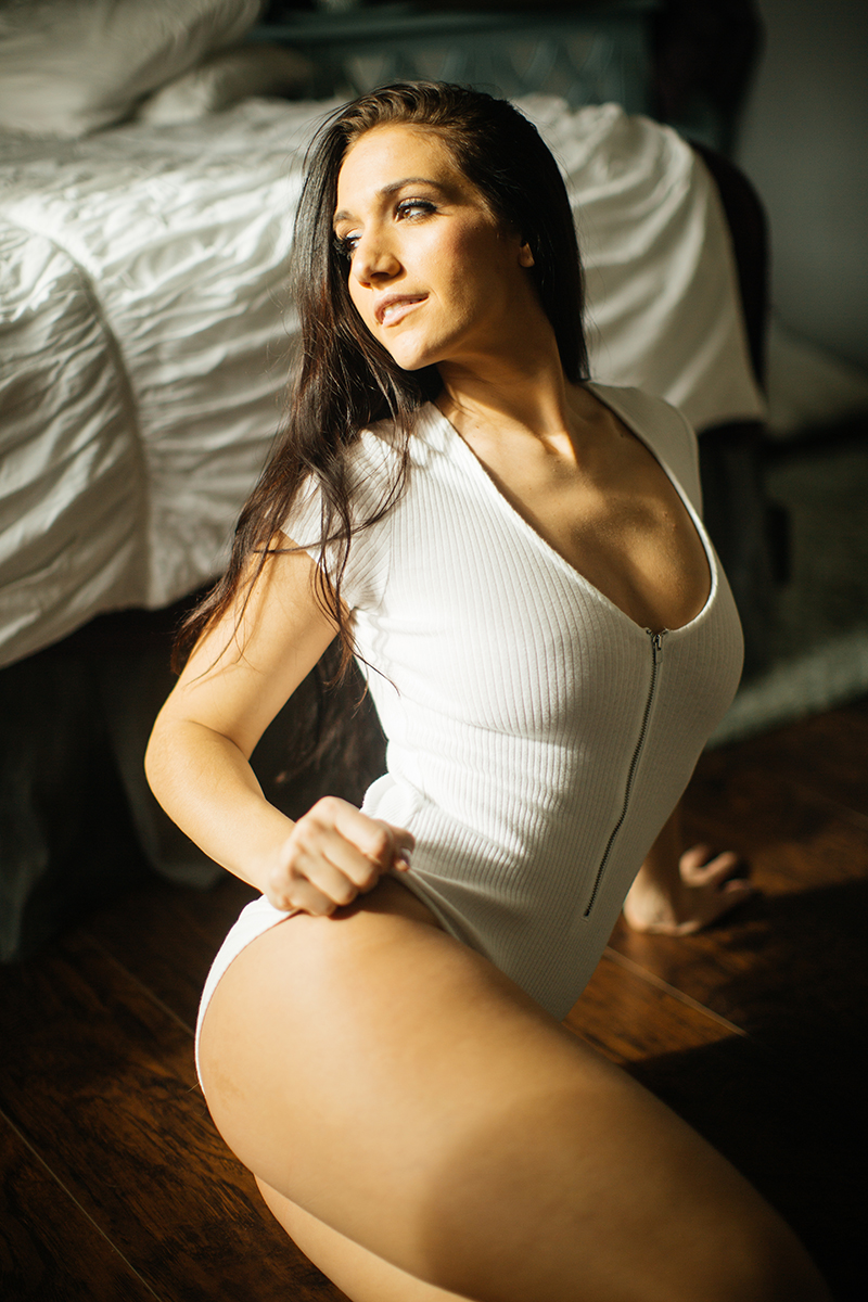 A beautiful young brunette poses for a Denver home studio boudoir photography wearing a white body suit in sitting on wood floor in Thornton, Colorado