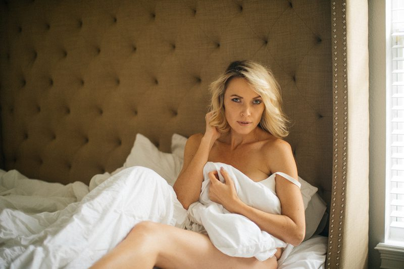 A beautiful blonde woman poses for an Orlando home boudoir photography session wearing a white bra on her bed wrapped up in her sheets in Florida