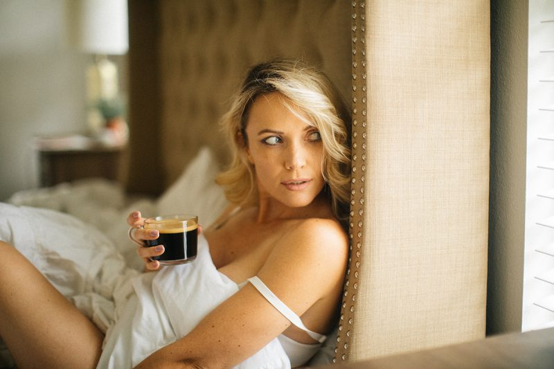 A beautiful blonde woman poses for an Orlando home boudoir photography session holding coffee wearing a white bra on her bed wrapped up in her sheets in Florida