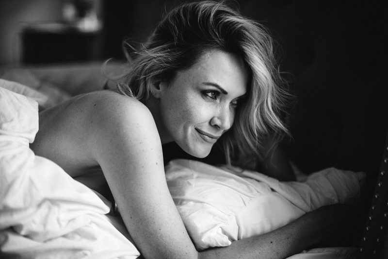 A beautiful blonde woman poses topless for an Orlando home boudoir photography session holding coffee on her bed wrapped up in her sheets in Florida