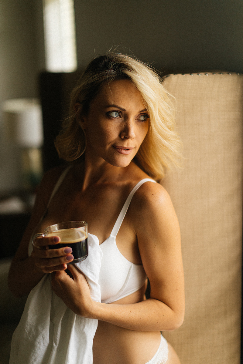 A beautiful blonde woman poses for an Orlando home boudoir photography session holding coffee wearing a white bra standing next to her bed wrapped up in her sheets in Florida