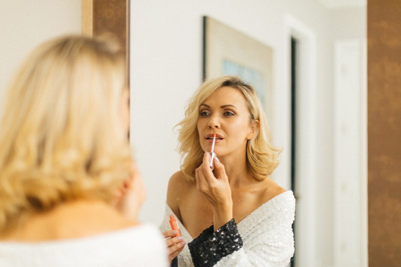 A beautiful blonde woman poses topless for an Orlando home boudoir photography session wearing a white robe while putting on lip gloss in front of a mirror in Florida