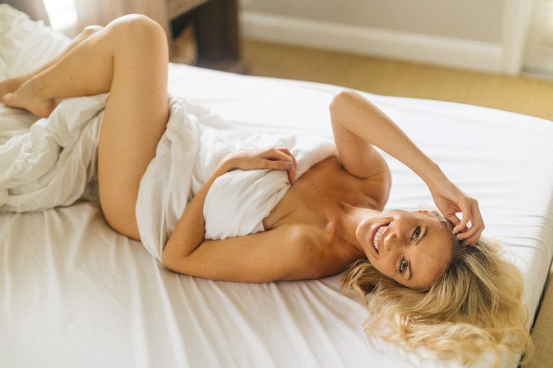 A beautiful blonde woman poses nude for an Orlando home boudoir photography session on her bed wrapped up in her sheets in Florida