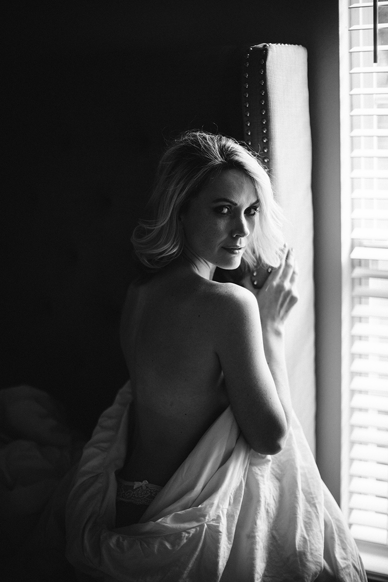 A beautiful blonde woman poses nude for an Orlando home boudoir photography session sitting on her bed wrapped up in her sheets in Florida