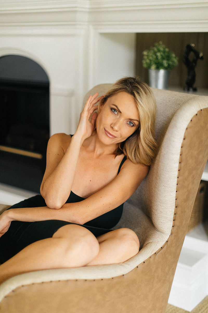 A beautiful blonde woman poses for an Orlando home boudoir photography session wearing a black dress sitting on a chair in her living room in front of a fireplace in Florida