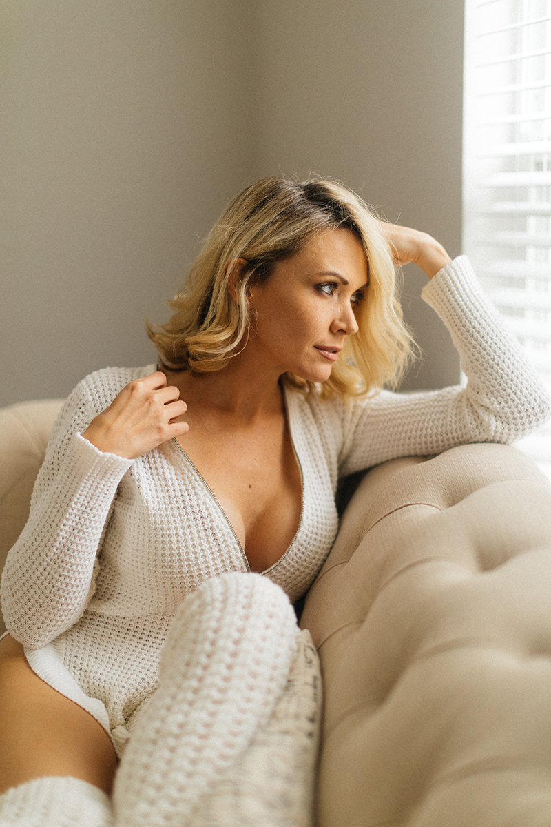 A beautiful blonde woman poses for an Orlando home boudoir photography session wearing a white sweater and white knee high socks sitting on a white couch in her living room in Florida