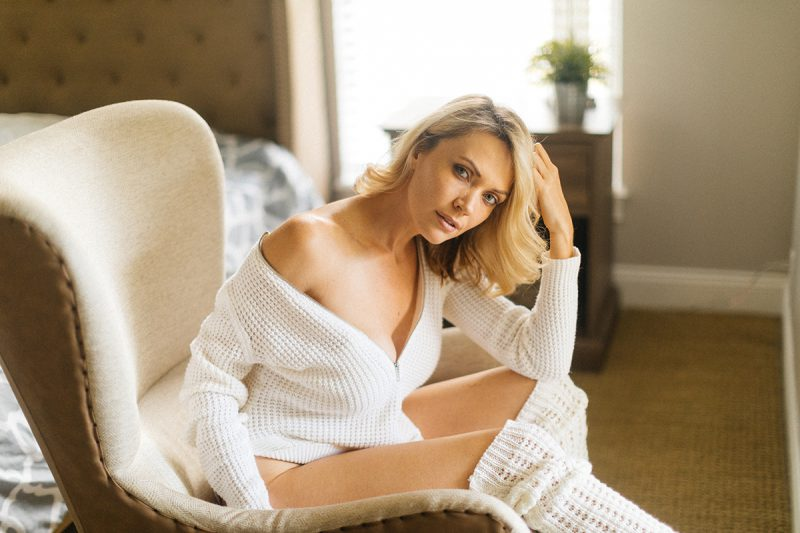 A beautiful blonde woman poses for an Orlando home boudoir photography session wearing a white sweater and white knee high socks sitting on a white chair in her bedroom in Florida