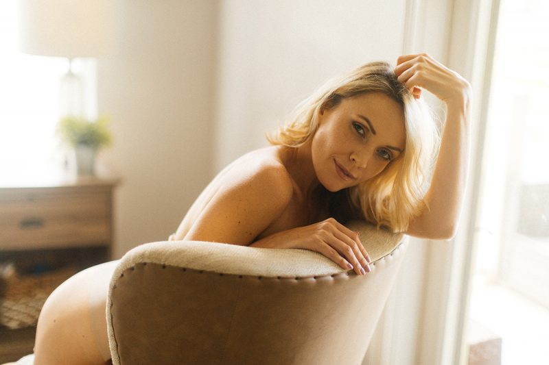 A beautiful blonde woman poses topless for an Orlando home boudoir photography session kneeling on a white chair in her bedroom in Florida