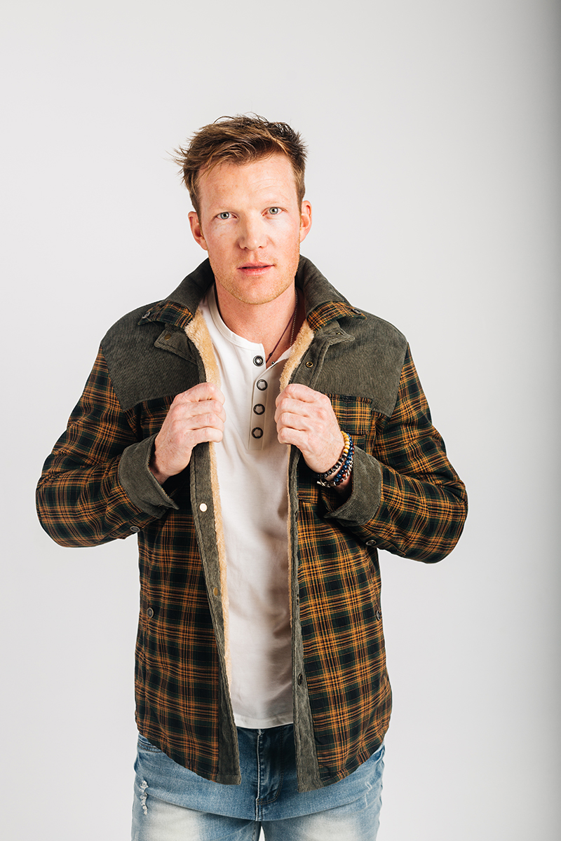 A handsome young blonde male model poses for a RAW Photographic Studio photography session in Denver Colorado wearing a yellow and green plaid jacket, a white button shirt and jeans