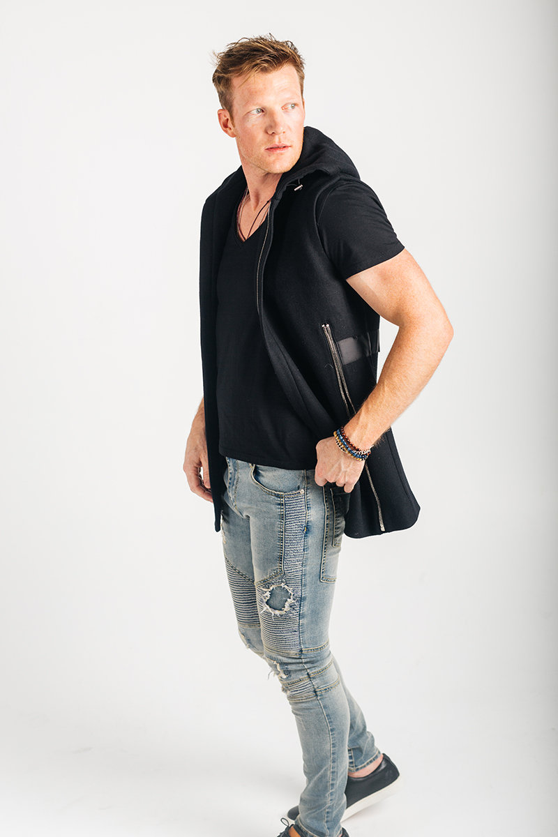 A handsome young blonde male model poses for a RAW Photographic Studio photography session in Denver Colorado wearing a black jacket, a black shirt and jeans