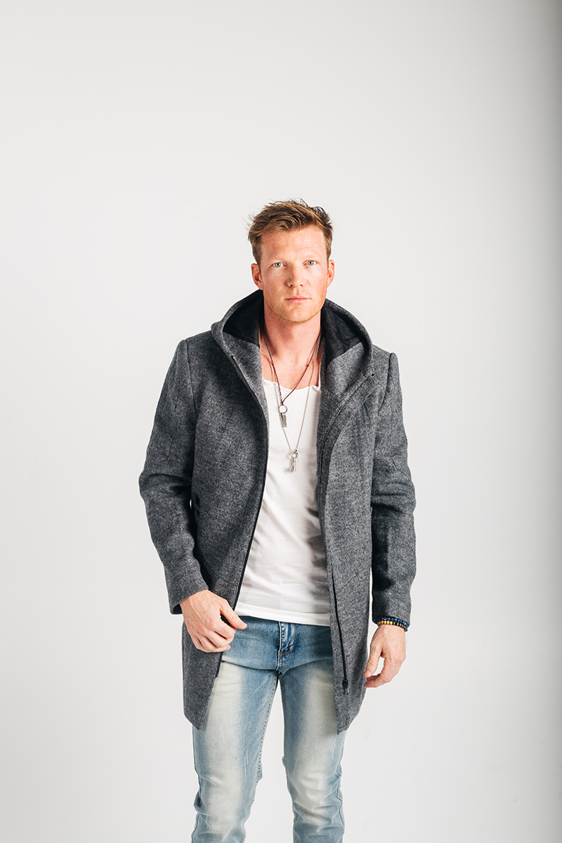 A handsome young blonde male model poses for a RAW Photographic Studio photography session in Denver Colorado wearing a gray jacket, a white shirt and jeans