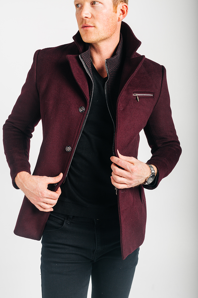A handsome young blonde male model poses for a RAW Photographic Studio photography session in Denver Colorado wearing a maroon peacoat, a black shirt and black pants