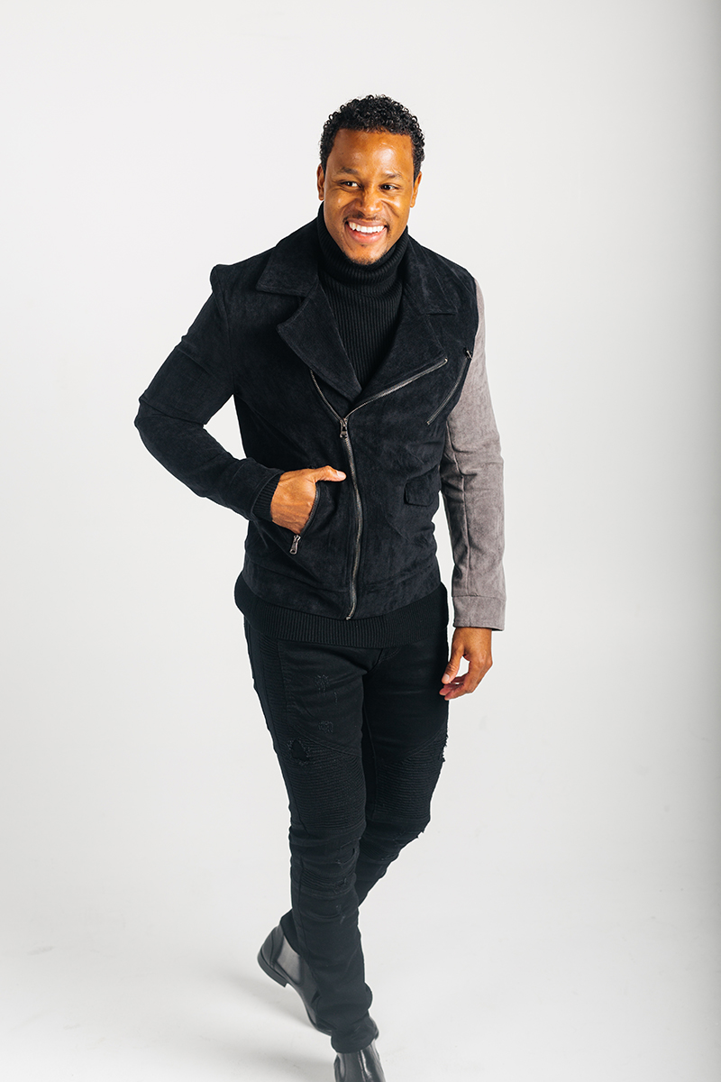 A handsome young brown haired male model poses for a RAW Photographic Studio photography session in Denver Colorado wearing a black and gray zipper jacket, a black turtleneck shirt and black pants