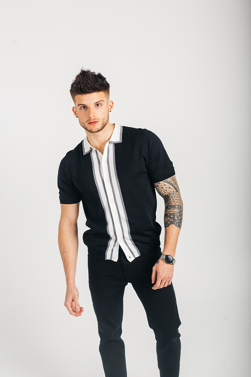 A handsome young brown haired male model poses for a RAW Photographic Studio photography session in Denver Colorado wearing a white and black button up shirt and black pants