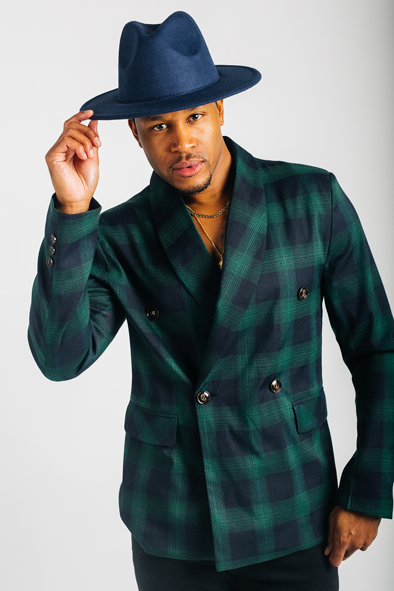 A handsome young brown haired male model poses for a RAW Photographic Studio photography session in Denver Colorado wearing a green and blue jacket, a black v-neck shirt, black pants and a blue fedora hat