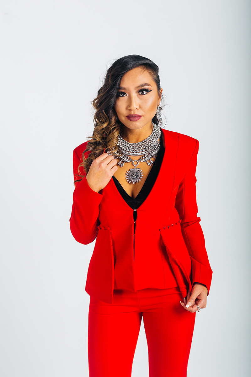 A beautiful young brunette model poses for a RAW Photographic Studio photography session in Denver Colorado wearing a beautiful necklace, a red jacket, red pants and a black tank top