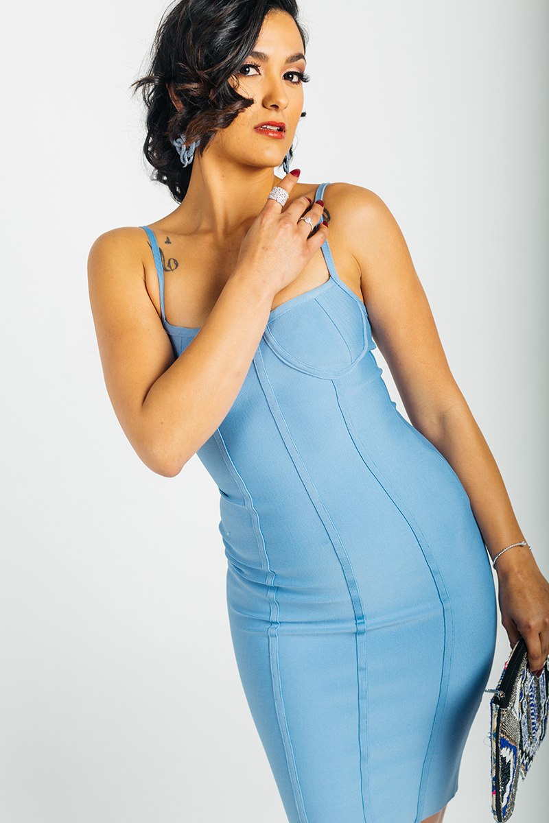 A beautiful young brunette model poses for a RAW Photographic Studio photography session in Denver Colorado wearing a blue dress holding a purse