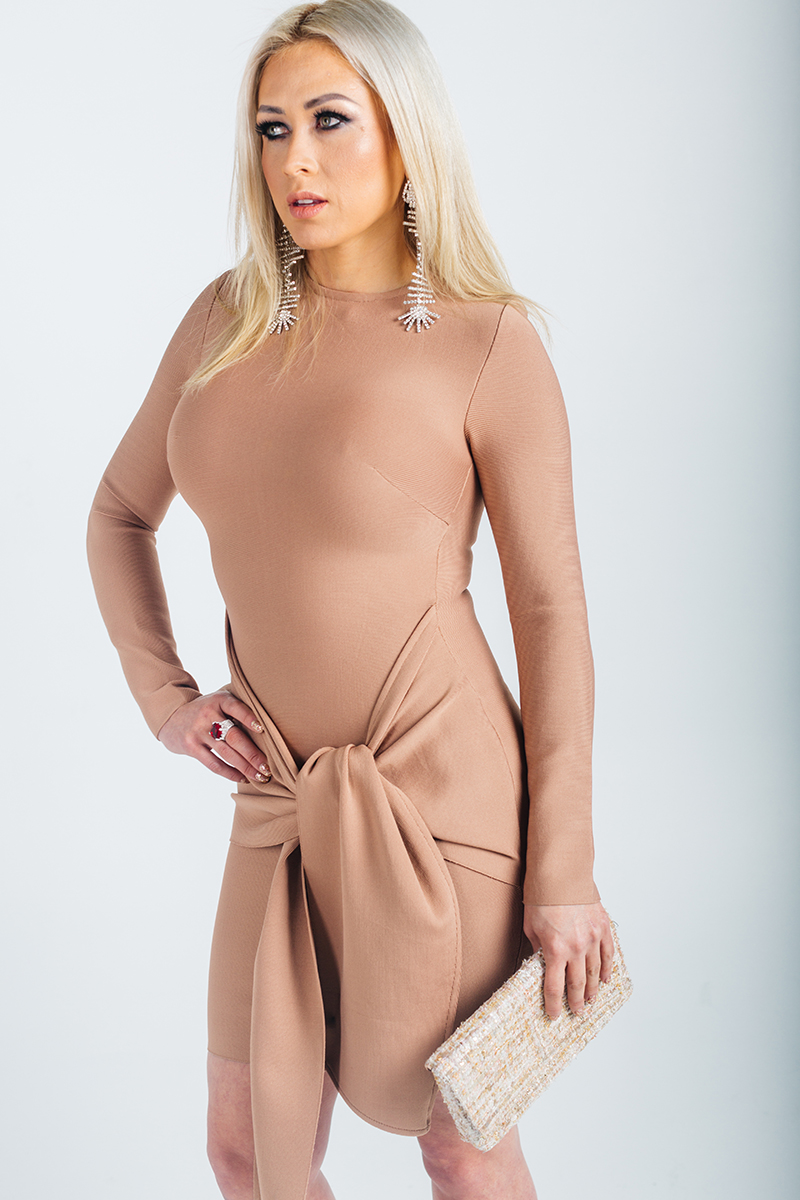 A beautiful young blonde model poses for a RAW Photographic Studio photography session in Denver Colorado wearing a mauve dress