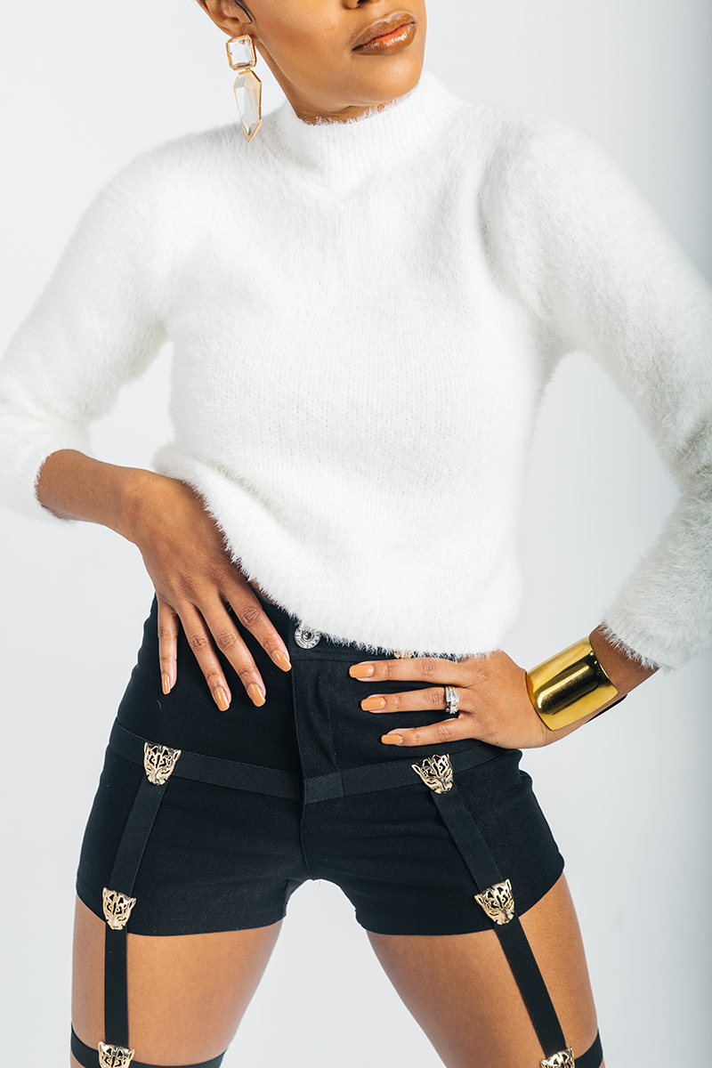 A beautiful young brunette model poses for a RAW Photographic Studio photography session in Denver Colorado wearing a white sweater and black shorts