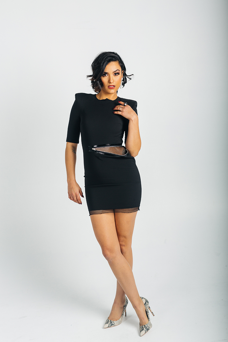 A beautiful young brunette model poses for a RAW Photographic Studio photography session in Denver Colorado wearing a black dress